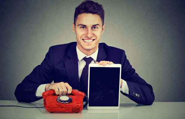 Handsome Business Man Sitting At Desk With Telephone And Tablet Computer