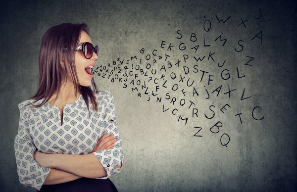 Woman In Sunglasses Talking With Alphabet Letters Coming Out Of Her Mouth.