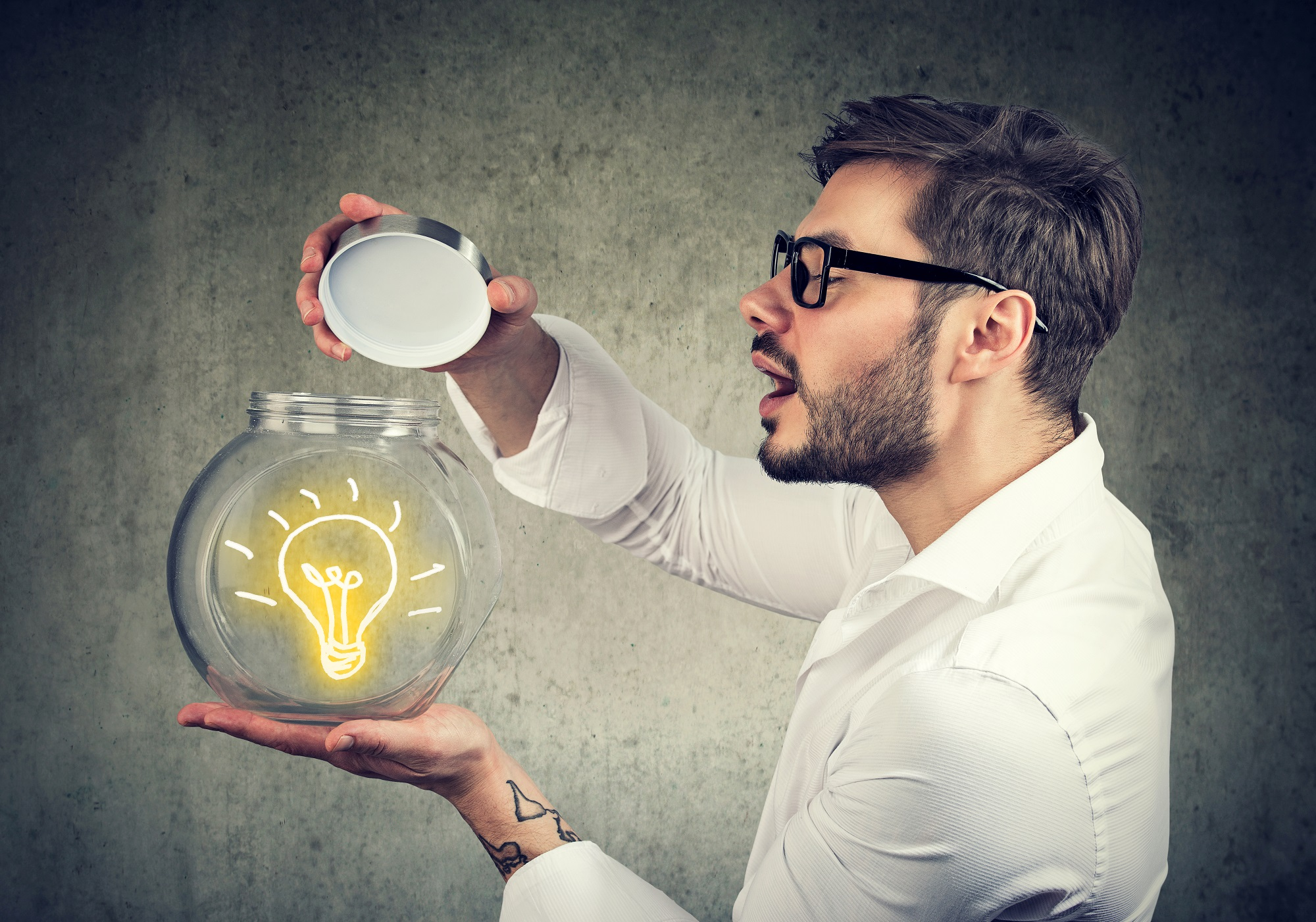 Excited Man Holding Opening A Glass Jar With Bright Idea Lighbulb Inside